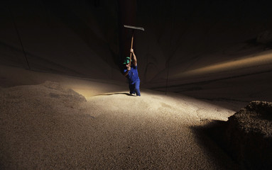 Man works in a mountain of soybeans stocked in the city of Sorriso