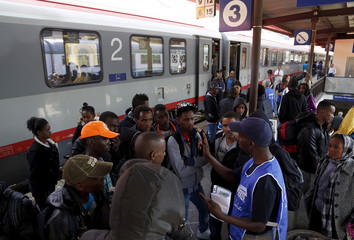 Volunteer talks to a group of migrants as police offficers stand in front of the door of a train bound for Munich, Germany, at Bolzano railway station, Italy