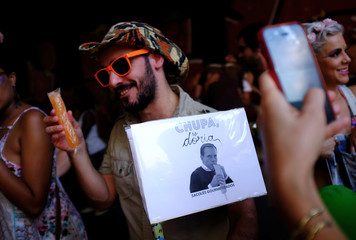 """A reveller sells an ice popsicle as he holds an image of new Sao Paulo Mayor Joao Doria that reads """"Suck Doria"""" during the annual block party in Sao Paulo"""