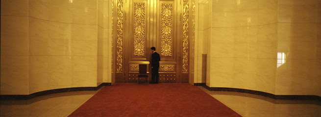 A security person closes a door as he guards an area of the Great Hall of the People, the venue of the 18th National Congress of the Communist Party of China in Beijing