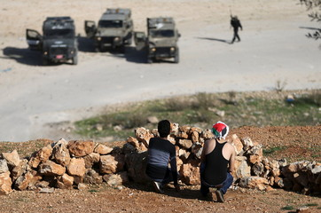 Palestinian protesters take cover during clashes with Israeli troops near Israel's Ofer Prison near Ramallah