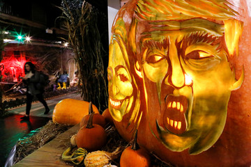 A woman passes by a giant pumpkins with the faces of 2016 Democratic nominee Hillary Clinton and Republican presidential nominee Donald Trump at Chelsea Market in New York