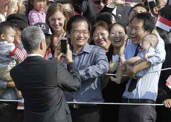 Singapore Prime Minister Lee Hsien Loong takes picture of family during arrival ceremony at the White House in Washington.