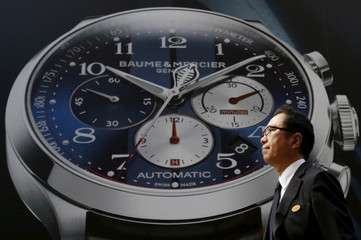 A man walks past an advertisement board for a luxury watch at Tokyo's Ginza shopping district
