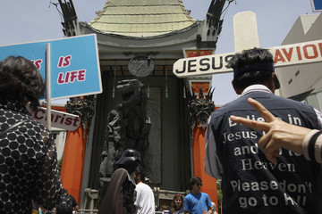 A parade of evangelical Christians chant religious slogans as a man dressed as the Star Wars character Darth Vader passes near a statue of movie monster Godzilla in front of the TCL Chinese Theatre IMAX forecourt in Hollywood