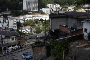 Policeman patrol the Casa Branca slum, with the Hospital de Sao Francisco de Assis in the background, in Rio de Janeiro
