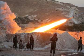 A file photo shows Free Syrian Army fighters launching a Grad rocket from Halfaya town in Hama province, towards forces loyal to Syria's President Bashar al-Assad stationed in Zein al-Abidin mountain