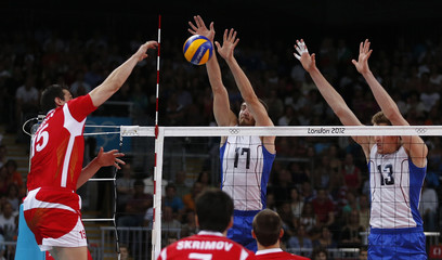 Bulgaria's Aleksiev spikes the ball against Russia's Mikhaylov and Muserskiy during their men's semi-final volleyball match at Earls Court during the London 2012 Olympic Games