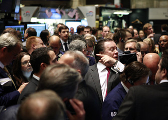 Traders gather at the kiosk where Pandora internet radio is traded prior to its debut on the floor of the New York Stock Exchange