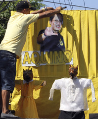 A supporter of senator and presidential candidate Benigno 'Noynoy' Aquino Jr., fix his picture in front of a roasted pig during the annual Lechon (roasted) pig parade in La Loma