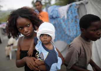 A woman carries her baby in a makeshift camp in Port-au-Prince