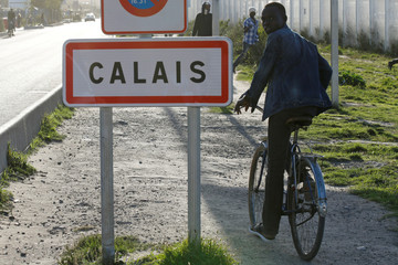 "A migrant passes by a road sign as he leaves the northern area of the camp called the ""Jungle"" in Calais"