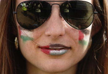 A demonstrator with her lips painted with the colours of the Palestinian flag protests in support of the people of Gaza, in central London