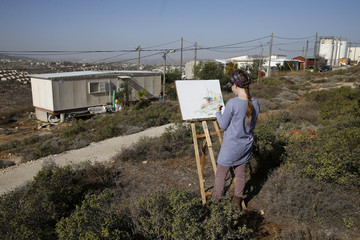 Hanna Horowitz an Israeli resident of the Jewish settler outpost of Amona in the West Bank draws a picture of the landscape in front a caravan