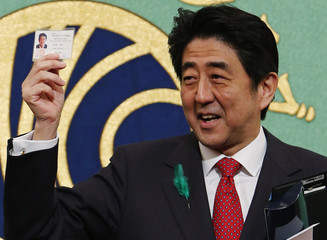 Japan's PM Abe holds his honorary membership card of the Japan National Press Club after receiving it following a news conference in Tokyo