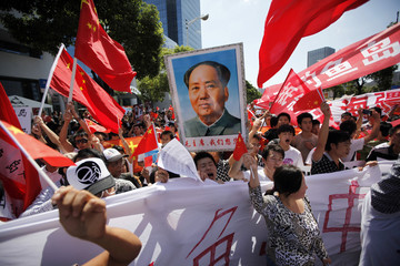 Protesters hold posters of China's late Chairman Mao Zedong and Chinese national flags as they shout slogans near the Japanese consulate during a protest in Shanghai