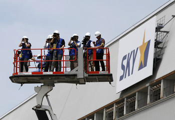 Photographers on a crane take pictures next to a logo of Skymark Airlines Inc at Haneda airport in Tokyo