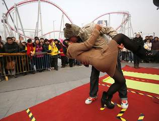 A couple participates during a kissing contest held in celebration of Valentine's Day at the Happy Valley amusement park in Beijing