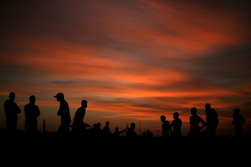 Palestinians watch youths as they demonstrate their parkour skills at Shati refugee camp in Gaza City