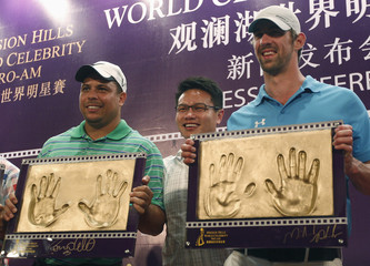 Former Brazilian national soccer player Ronaldo Chairman and CEO of Mission Hills group Chu and U.S. Olympic swimmer Phelps pose pose for picture during Mission Hills World Celebrity Pro-Am tournament in Haikou