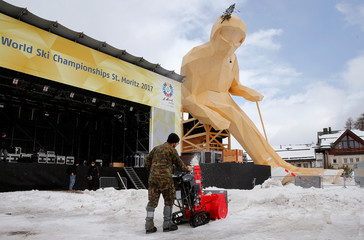 A soldier of the Swiss Army uses a snow blower to remove snow in front of a giant wooden sculpture of a ski racer, before the upcoming FIS Alpine World Ski Championships 2017 in the mountain resort of St. Moritz