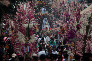 Catholics take part in a procession during the celebration of the Palms and Flowers Festival in Panchimalco