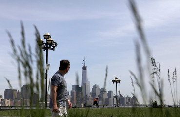 New York's One World Trade Center stands tall on the skyline of Lower Manhattan as a man walks through a park in Hoboken, New Jersey