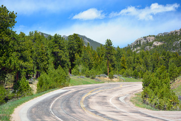 Curved Weathered Asphalt Mountain Road on a Sunny Day