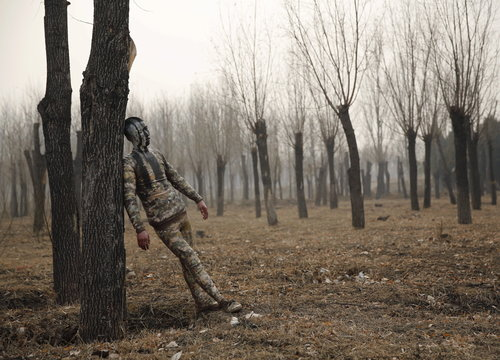 """A model painted in camouflage colours to blend in with the background practises posing for Chinese artist Liu Bolin's artwork """"Dongji"""", or Winter Solstice, in Beijing"""