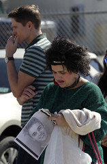 A woman holds an image of teen pop star Justin Bieber outside the Miami-Dade County jail where Bieber was being held in Miami