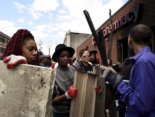 People work together to clean up the CVS Pharmacy building on Pennsylvania Avenue in Baltimore