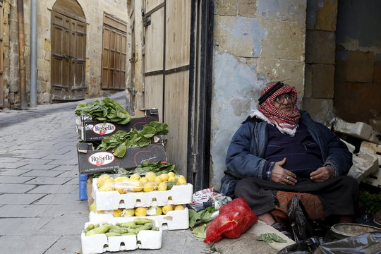 A vegetable seller waits for customers in his shop at the Hammam Street Market, on one of the oldest commercial streets in Salt, Jordan