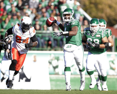 Saskatchewan Roughriders Darian Durant is chased by BC Lions defensive tackle Khreem Smith during the first half of their CFL football game in Regina