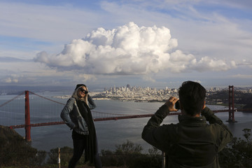 Visitors to the Marin Headlands pose for photographs overlooking the Golden Gate Bridge and skyline of San Francisco, as a large cloud gathers over the city