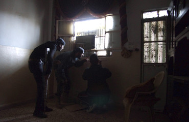 A Free Syrian Army fighter gestures, as his colleague holds his camera inside a house in Deir al-Zor