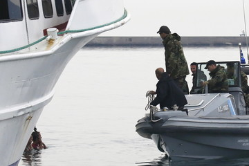 Greek Coast Guard officers on a speedboat approach activists hanging from the anchor's chain of a Turkish-flagged passenger boat carrying migrants to be returned to Turkey, in an attempt to prevent it from leaving the port of Mytilene, on island of Lesbos