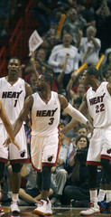 The Miami Heat's  Guard Dwayne Wade celebrates a basket with teammates Chris Bosh and James Jones against the Philadelphia 76ers' during the second half of their NBA basketball game in Miami, Florida