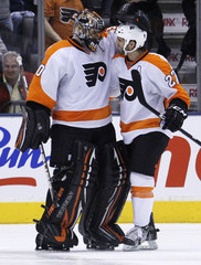 Flyers' goalie Bryzgalov is congratulated by his teammate Talbot on his shutout win against the Maple Leafs during their NHL hockey game in Toronto