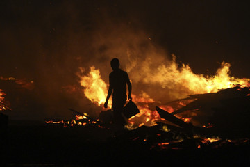 A man holds a bucket as he tries to extinguish a late night fire at the Okobaba sawmill near the Lagos Lagoon