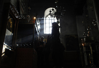 A tourist looks at a picture of the Virgin Mary as she visits the Church of the Nativity in Bethlehem