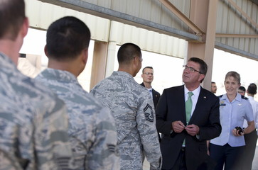 U.S. Defense Secretary Ash Carter, joined by Col. Jeannie Leavitt, hands out challenge coins as he meets with U.S. troops at a Jordanian Air Base