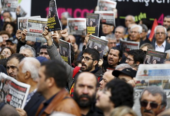Demonstrators shout slogans during a protest outside the Cumhuriyet newspaper headquarters in Istanbul