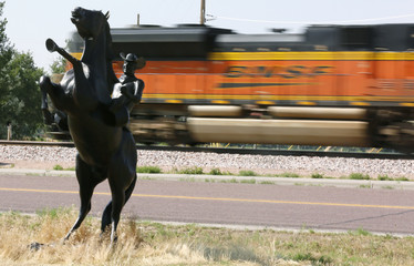 A BNSF train rolls by a statue of the state symbol of the state of Wyoming, a bucking bronco, in Ft. Laramie