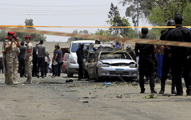 Policemen and army forces are seen at the site of a car bomb attack on the convoy of Egyptian public prosecutor Hisham Barakat near his house at Heliopolis district in Cairo