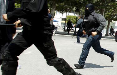 Riot police chase after anti-government protesters in Tunis