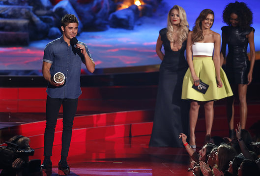 """Zac Efron accepts the award for best shirtless performance for """"That Awkward Moment"""" at the 2014 MTV Movie Awards in Los Angeles"""