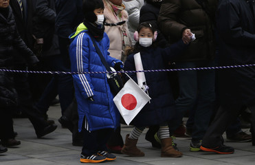 Children holding Japan's national flag arrive for New Year celebrations at the Imperial Palace in Tokyo