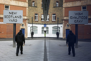 A man walks past the rotating triangular sign outside New Scotland Yard in central London