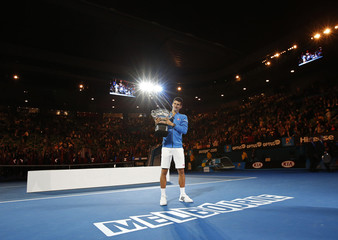 Djokovic of Serbia holds up his trophy after defeating Murray of Britain to win their men's singles final match at the Australian Open 2015 tennis tournament in Melbourne