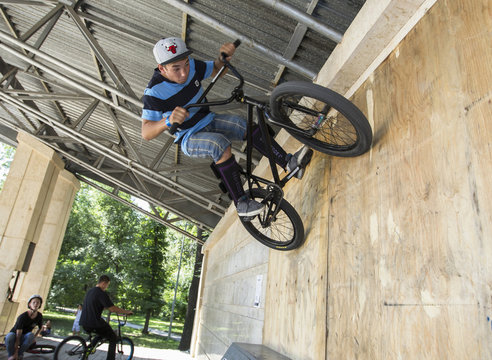 A rider practices BMX during Red Bull Local Hero skateboarding and BMX festival in a park in Almaty